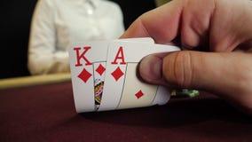 Kartenkombination, -as und -könig der Pokerspielervertretung gute auf Schürhakentabelle Nahaufnahme des Mannes Hand Kasinoglückss stock video footage