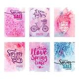 Kartensatz Frühlingsverkäufe auf einem Blumenaquarellhintergrund Satz Ikonen, Fahrrad, Herz Typografieplakat, Aufkleber, Fahne Lizenzfreies Stockfoto