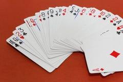 Kartenspiele auf rotem Hintergrund Spielen und Konzept wettend Stockfotografie