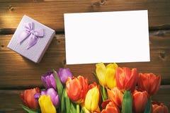 Kartenspott des leeren Papiers oben mit einer Geschenkbox und Tulpen auf einem Holztisch Stockbilder