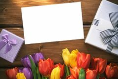 Kartenspott des leeren Papiers oben mit einer Geschenkbox und Tulpen auf einem Holztisch Lizenzfreie Stockbilder