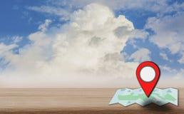 Kartenzeigerikone setzte auf einen Holztisch, Hintergrund ist heller blauer Himmel, Tageslicht und Kumuluswolken, mit dem Konzept stockfotografie