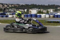 Karting冠军 头戴盔甲的karts的司机,赛跑衣服参加kart种族 Karting展示 孩子 免版税库存照片