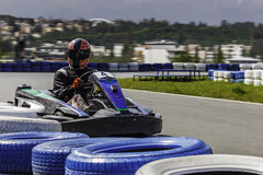 Karting冠军 头戴盔甲的karts的司机,赛跑衣服参加kart种族 Karting展示 孩子 库存图片