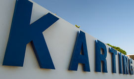 Karting in big blue letters on a white wall. Big blue sign made of individual letters creating the word karting with a clear blue sky Stock Photo