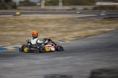 Karting - conductor en casco en el circuito del kart foto de archivo