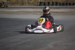 Karting - conductor en casco en el circuito del kart fotografía de archivo