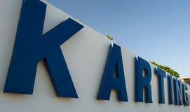 Karting dans de grandes lettres bleues sur un mur blanc Photo stock