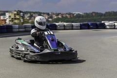 Karting-Meisterschaft Fahrer in den karts, die den Sturzhelm, Anzug laufend tragen, nehmen an kart Rennen teil Karting-Show Kinde Lizenzfreie Stockfotografie