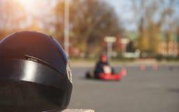 Kartingscompetities, zwarte het rennen helm tegen de achtergrond van het karting van competities, actie stock foto's