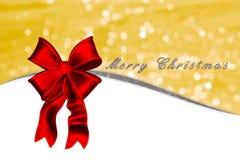 Kartka bożonarodzeniowa z czerwonym łęku i srebra tekstem na złotym tle Zdjęcie Stock