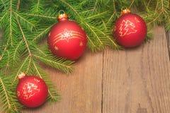 Kartka bożonarodzeniowa z jedlinowym drzewem i boże narodzenie czerwonymi piłkami na drewnianym b Zdjęcie Royalty Free