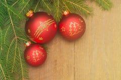 Kartka bożonarodzeniowa z jedlinowym drzewem i boże narodzenie czerwonymi piłkami na drewnianym b Obrazy Stock