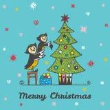 Kartka bożonarodzeniowa z ręka rysującym sowa rodzicem, dzieckiem dekoruje choinki i royalty ilustracja