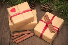Kartka bożonarodzeniowa z trzy teraźniejszość, cynamon i jedlinowy drzewo, na drewnie Obraz Royalty Free