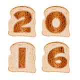 2016 kartka z pozdrowieniami na wznoszących toast plasterkach odizolowywających na bielu chleb Obraz Royalty Free