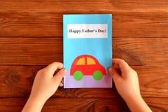 Kartka z pozdrowieniami ojca dzień Dziecko trzyma kartka z pozdrowieniami w jego ręce ojciec jest szczęśliwy dzień Łatwi dzieciak Zdjęcia Royalty Free