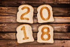 2018 kartka z pozdrowieniami wznosił toast plasterki chleb na drewnianych deskach Zdjęcia Royalty Free