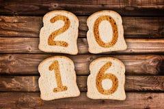 2016 kartka z pozdrowieniami wznosił toast plasterki chleb na drewnianych deskach Zdjęcia Stock