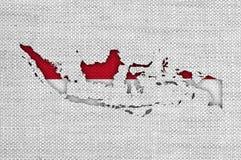 Kartlägga och flaggan av Indonesien på gammal linne arkivfoton