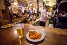 Kartoffel Tapas auf Platte und Glas Bier für Kunden des beschäftigten Schnellrestaurants in der traditionellen spanischen Art stockfoto