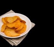 Kartoffelchips auf weißem Teller auf schwarzem Hintergrund mit Kopienraum stockfotografie