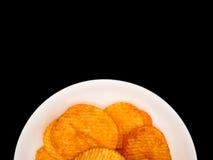 Kartoffelchips auf weißem Teller auf schwarzem Hintergrund mit Kopienraum Stockfoto