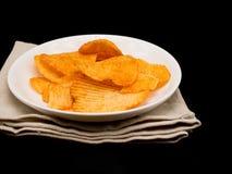 Kartoffelchips auf weißem Teller auf schwarzem Hintergrund mit Kopienraum lizenzfreie stockfotografie