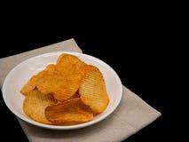 Kartoffelchips auf weißem Teller auf schwarzem Hintergrund mit Kopienraum Lizenzfreies Stockbild
