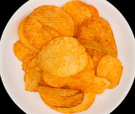 Kartoffelchips auf weißem Teller auf schwarzem Hintergrund mit Kopienraum Lizenzfreie Stockbilder