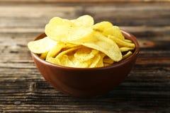 Kartoffelchips in der Schüssel auf braunem hölzernem Hintergrund Lizenzfreie Stockbilder