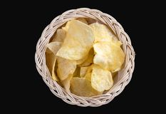 Kartoffelchips in einem Korb gemacht vom Rattan auf einem schwarzen Hintergrund Lizenzfreie Stockfotos