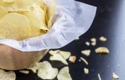Kartoffelchips in einer Schüssel hergestellt vom Holz auf einem schwarzen Hintergrund Stockfotos