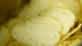 Kartoffelchips ist Imbiss in der essfertigen und fetten Nahrung der Tasche oder in der ungesunden Fertigkost rotate stock video footage