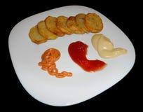 Kartoffelchips mit der Soße lokalisiert auf Schwarzem Lizenzfreies Stockfoto