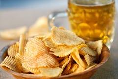 Kartoffelchips und Bier auf einem Holztisch lizenzfreies stockfoto