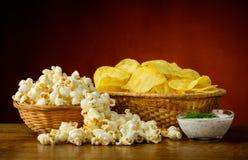 Kartoffelchips und Popcorn Lizenzfreie Stockfotos