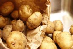 Kartoffeln in einem Sp?lbecken heraus gegossen aus einer Papiert?te lizenzfreie stockfotografie