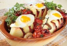 Kartoffeln, gebacken mit Speck, Pilzen und Tomaten Stockbilder