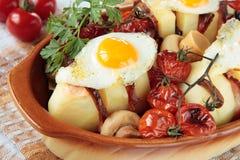 Kartoffeln, gebacken mit Speck, Pilzen und Tomaten Stockfotos