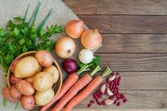Kartoffeln, Karotten, Zwiebeln auf dem Rausschmiß und Holztisch lizenzfreie stockbilder