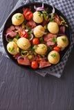 Kartoffeln mit gebratener Draufsichtvertikale des Speckes und der Tomaten Lizenzfreie Stockfotos