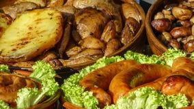Kartoffeln, Pilzchampignons und gegrillte Würste Stockfotos