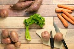 Kartoffeln, Süßkartoffeln, Karotten und Sellerie auf Holztisch für das Kochen Stockbilder