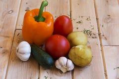 Kartoffeln, Tomaten, Pfeffer, Gurken und Knoblauch auf einer hölzernen SU Stockfoto