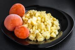 Kartoffeln und Tomaten auf einem Schwarzblech Lizenzfreie Stockfotografie