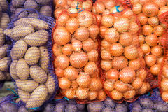 Kartoffeln und Zwiebeln in der Masche auf dem Markt Stockfoto