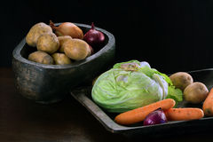 Kartoffeln, Zwiebeln, Karotten und Kohl in den hölzernen Schüsseln Stockfoto