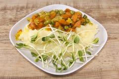 Kartoffelpürees mit gebratenen Karotten, Erbsen und frischen Sonnenblumensprösslingen Stockfotografie