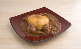 Kartoffelpürees mit Soßen- und Rindfleischtipps auf einer Platte Stockfotos